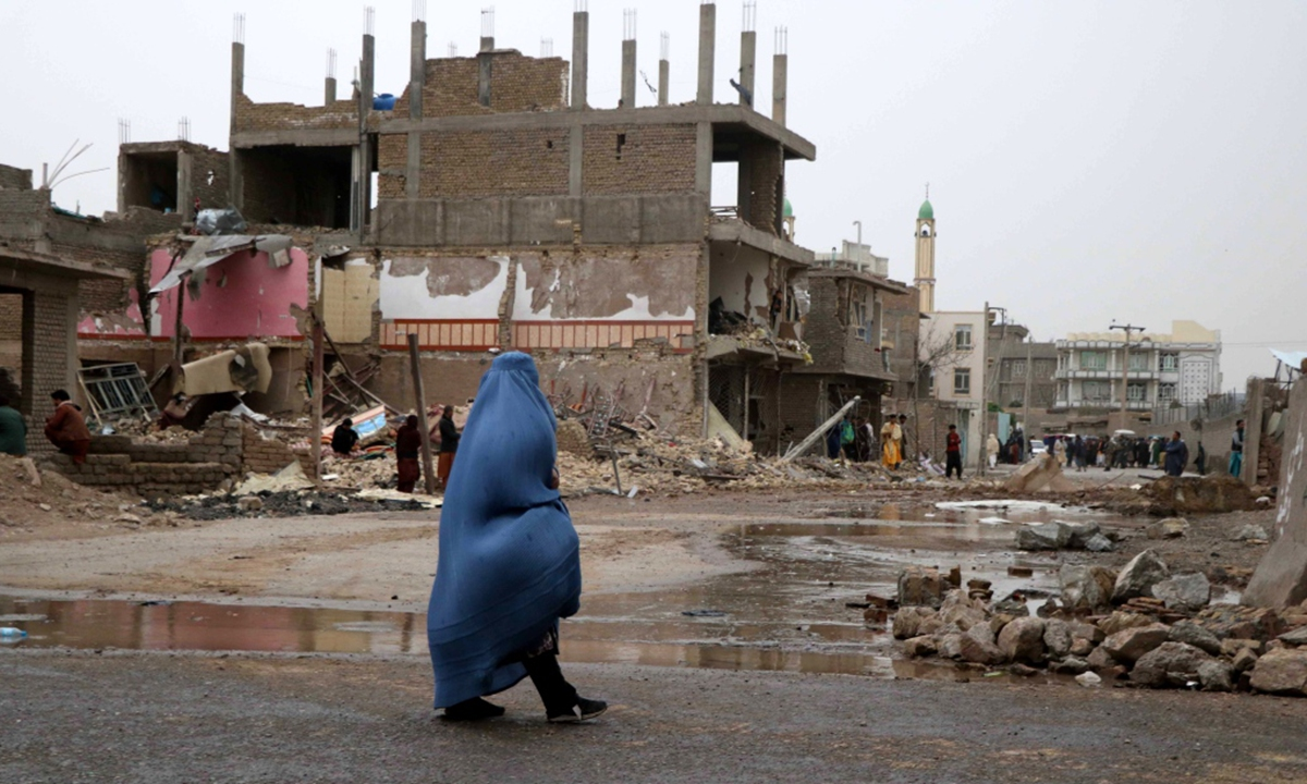 A woman observes the scene of an attack a day after a car bomb went off in Herat, Afghanistan, March 13, 2021. Photo: IC