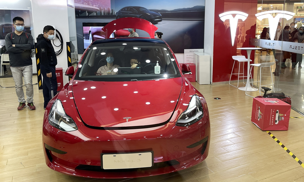 People sit inside a Tesla car displayed at a store in Beijing. Photos: VCG