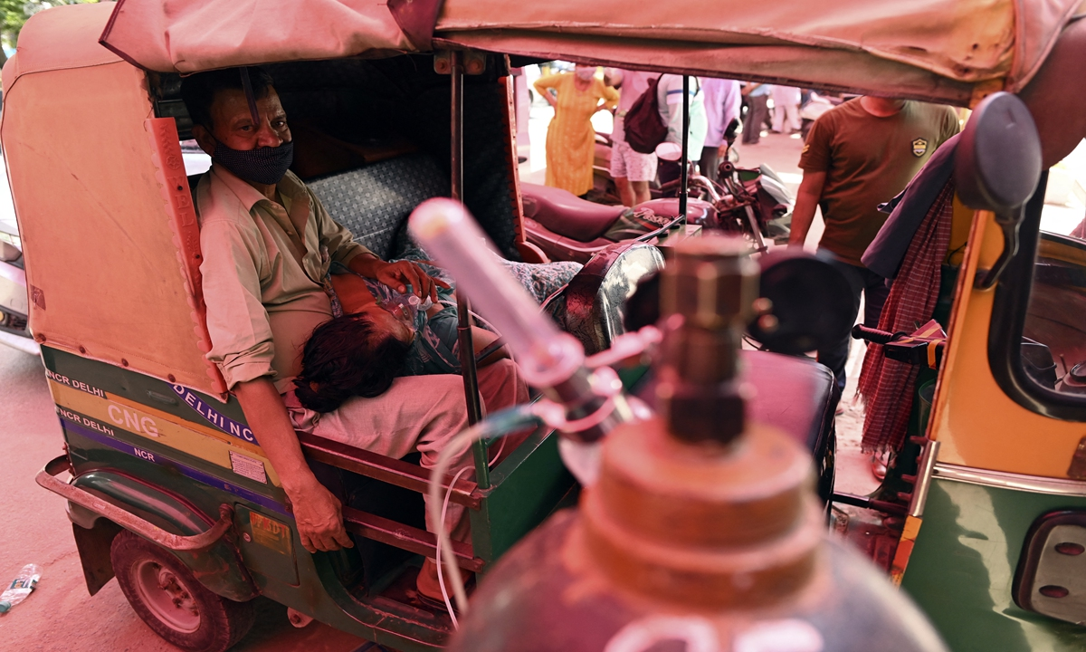 A patient breathes with the help of oxygen provided by a Gurdwara, a place of worship for Sikhs, inside an auto rickshaw parked under a tent along the roadside amid the COVID-19 coronavirus pandemic in Ghaziabad on Monday. Photo: VCG