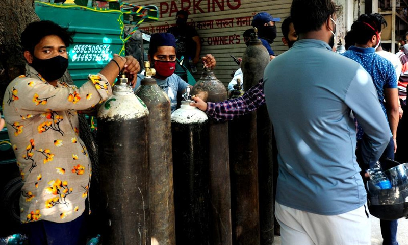 People wait in line to refill empty medical oxygen cylinders for COVID-19 patients in front of a shop in New Delhi, India, April 26, 2021.(Photo: Xinhua)
