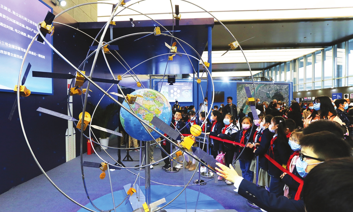 Young students take a close look at a model of the BeiDou global navigation network on Tuesday in Nanjing, capital of East China's Jiangsu Province. The space science popularization exhibition was officially opened to the public Tuesday. Photo: VCG