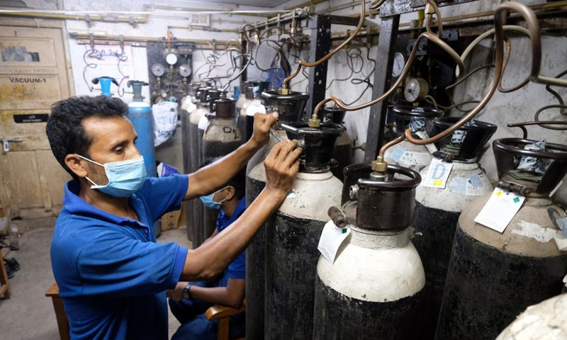 A hospital worker adjusts the oxygen cylinders to supply oxygen through the central pipeline for the patients at a private hospital in Kolkata, India, April 28, 2021.Photo:Xinhua