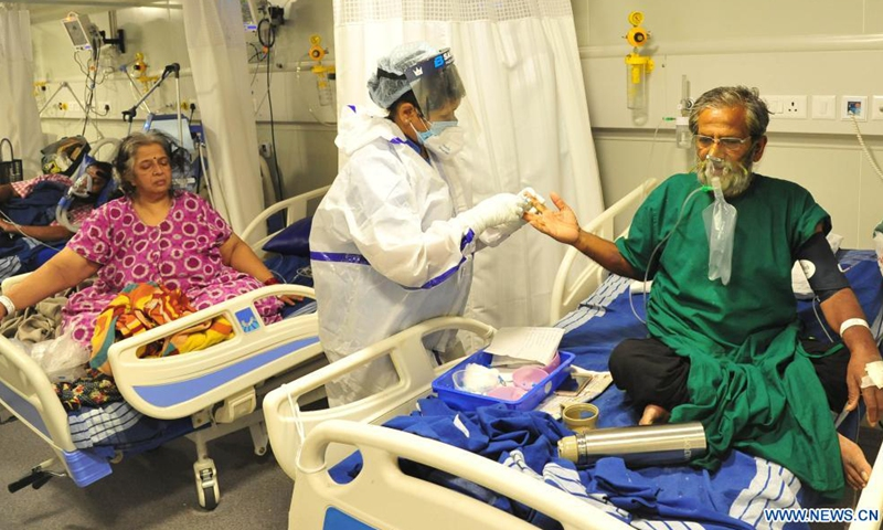 Patients receive treatment inside a COVID-19 ward in a hospital, in Bangalore, India, April 30, 2021. India's COVID-19 tally reached 19,164,969 on Saturday, with a single day spike of 401,993 cases, the health ministry said. This is the first time when over 400,000 new cases were recorded in India in 24 hours, and a record number of 3,523 deaths since Friday morning took the total death toll to 211,853. (Str/Xinhua)