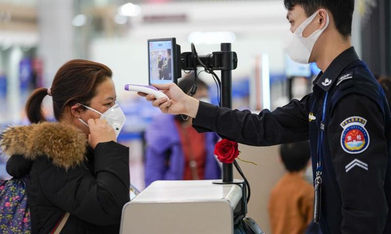 A security staff member checks a passenger's temperature at Chongqing Jiangbei International Airport in southwest China's Chongqing, Jan. 26, 2020. File photo: Xinhua