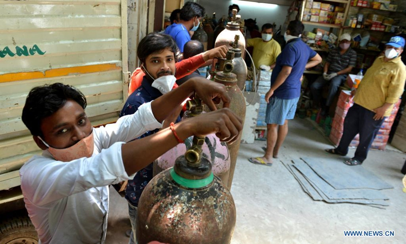 People wait to refill oxygen cylinders for COVID-19 patients at Jangpura area in New Delhi, India, on May 5, 2021.(Photo: Xinhua)