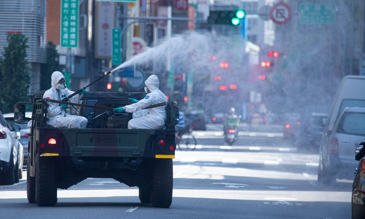 Disinfection workers sanitize the streets in Taipei on the island of Taiwan on Sunday amid mounting COVID-19 epidemic control pressure, as the island registered 335 cases on Monday following 207 the previous day. Photo: VCG
