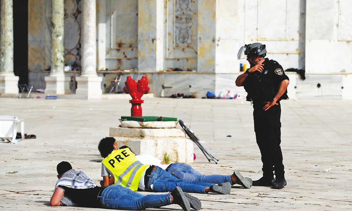 An Israeli policeman speaks with Palestinian youths lying prone on the ground at Jerusalem's Al-Aqsa mosque compound on Monday, after gunfire was shot amidst clashes with Israeli security forces ahead of a planned march to commemorate Israel's takeover of Jerusalem in the 1967 Six-Day War. Hundreds were wounded in new clashes Monday between Palestinians and Israeli security forces in Jerusalem. Photo: AFP