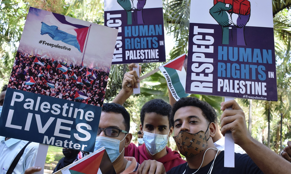 People hold placards during a peaceful procession in solidarity with the Palestinian people amid the ongoing conflict with Israel, in Mombasa, Kenya, on Monday. The conflict in the Gaza Strip has seen 198 Palestinians killed, including 58 children and 35 women, according to the Palestinian Ministry of Health on Monday. Photo: AP
