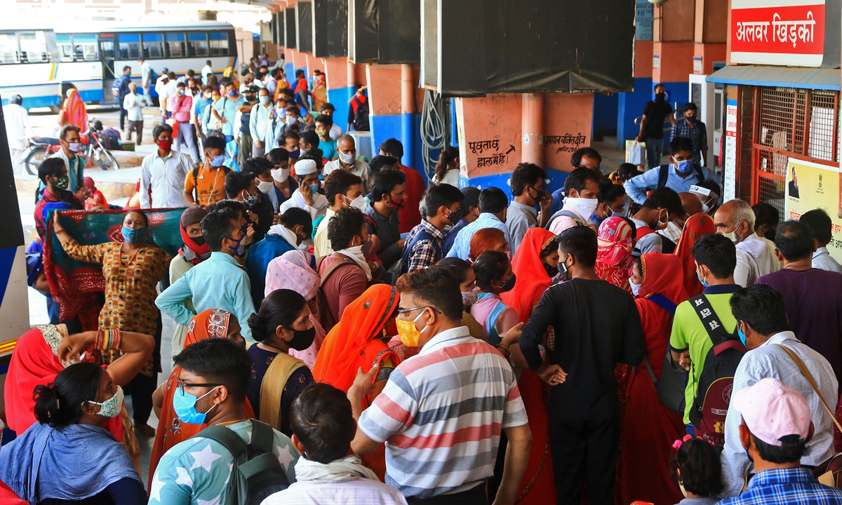 Passengers stand in a queue at a ticket counter to board buses for their native place, after authorities announced 14 Days lockdown , amid surge in coronavirus cases across the country, at Sindhi camp bus stand in Jaipur , Rajasthan, India, on Sunday, May 9,2021. Photo: VCG