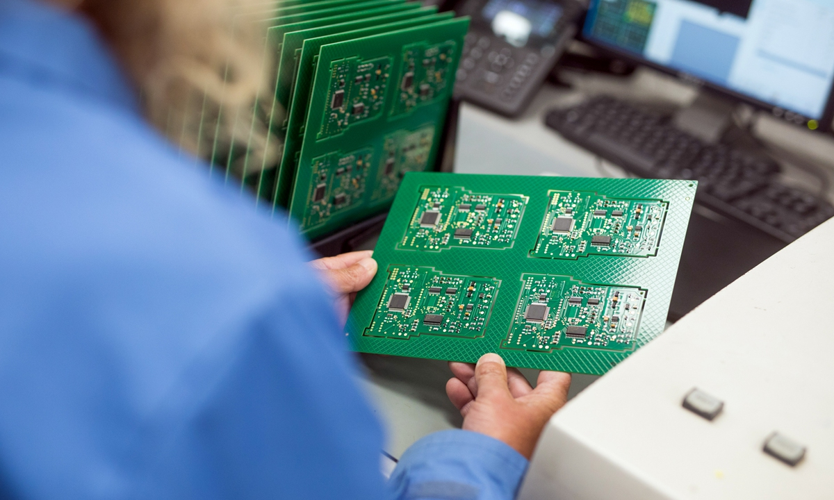 An employee checks a printed circuit board containing integrated circuit microchips at CSI Electronic Manufacturing Services Ltd. in Witham, the UK, on April 28, 2021. Photo: VCG