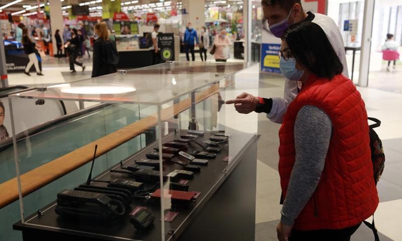 Oamenii se uită la telefoanele mobile vechi afișate într-un centru comercial din București, România, pe 12 mai 2021. A avut loc aici un afișaj de 14 zile al dispozitivelor de comunicație pentru a sărbători Ziua Mondială a Telecomunicațiilor și a Societății Informaționale, care cade pe 17 mai în fiecare an .  Spectacolul se va desfășura până pe 23 mai (Foto: Xinhua)