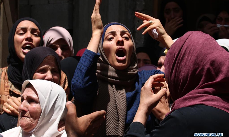 Relatives of a Palestinian teenager who was shot dead by Israeli soldiers during clashes mourn during the funeral in village of Aqqaba near the West Bank city of Tubas, on May 12, 2021.(Photo: Xinhua)
