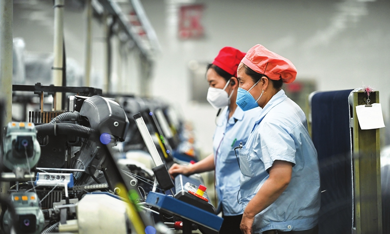 Women work at a denim fabric assembly line in Jinhua, East China's Zhejiang Province on Wednesday. The company's denim fabric production hit a new high in the first four months of the year, with exports, primarily to Europe, the Americas and Africa, soaring 78 percent year-on-year. Photo: cnsphoto