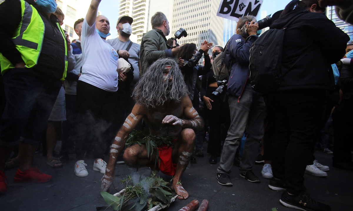 An Indigenous Australian participates in a smoking ceremony in front of Sydney Town Hall during a protest against Aboriginal deaths in custody in Sydney, Australia on June 6, 2020. Many thousands have rallied in Sydney CBD to stop Aboriginal deaths in custody after an appeal court's last-minute decision to authorise the public gathering. Photo: AFP