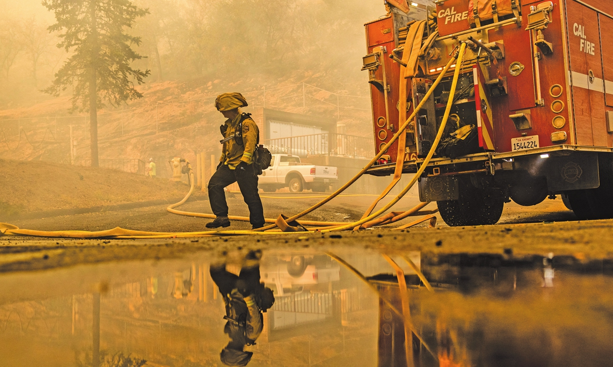 Firefighters with Cal Fire work to protect the St. Helena Water Treatment Plant from the Glass Fire in Napa Valley, California, the US, on September 27, 2020. Photo: AFP