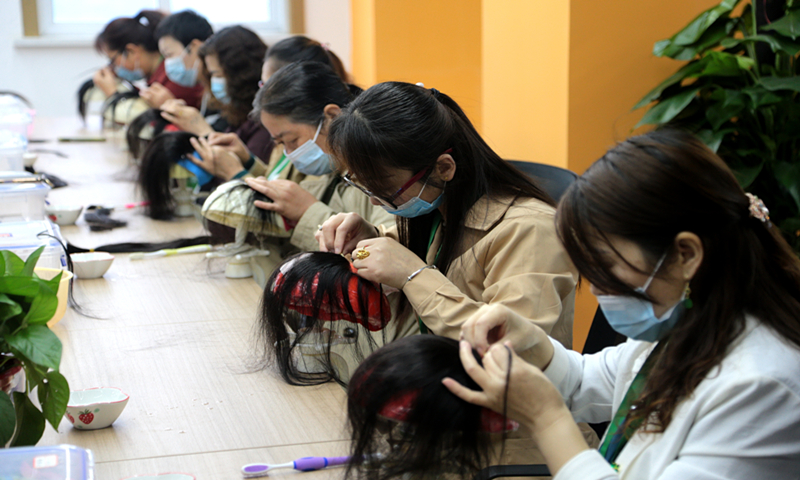 Workers produce wigs in a workshop in Northwest China's Shaanxi Province on May 16, 2021. Photo: VCG