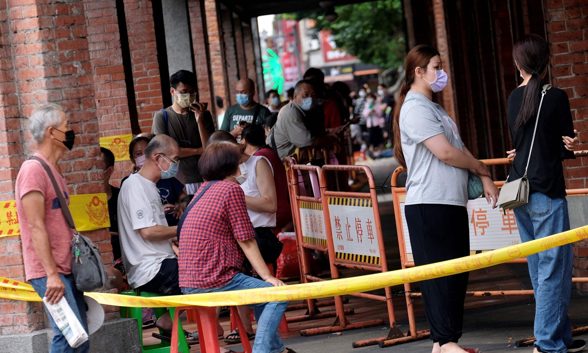 Residents on the island of Taiwan line up and wait for getting a COVID-19 nucleic acid test in Taipei on Tuesday. Testing on the island is 21 times more expensive than  the mainland, hindering epidemic control of the island, which reported 240 new infections Tuesday after a record of 333 cases the previous day. Photo: VCG
