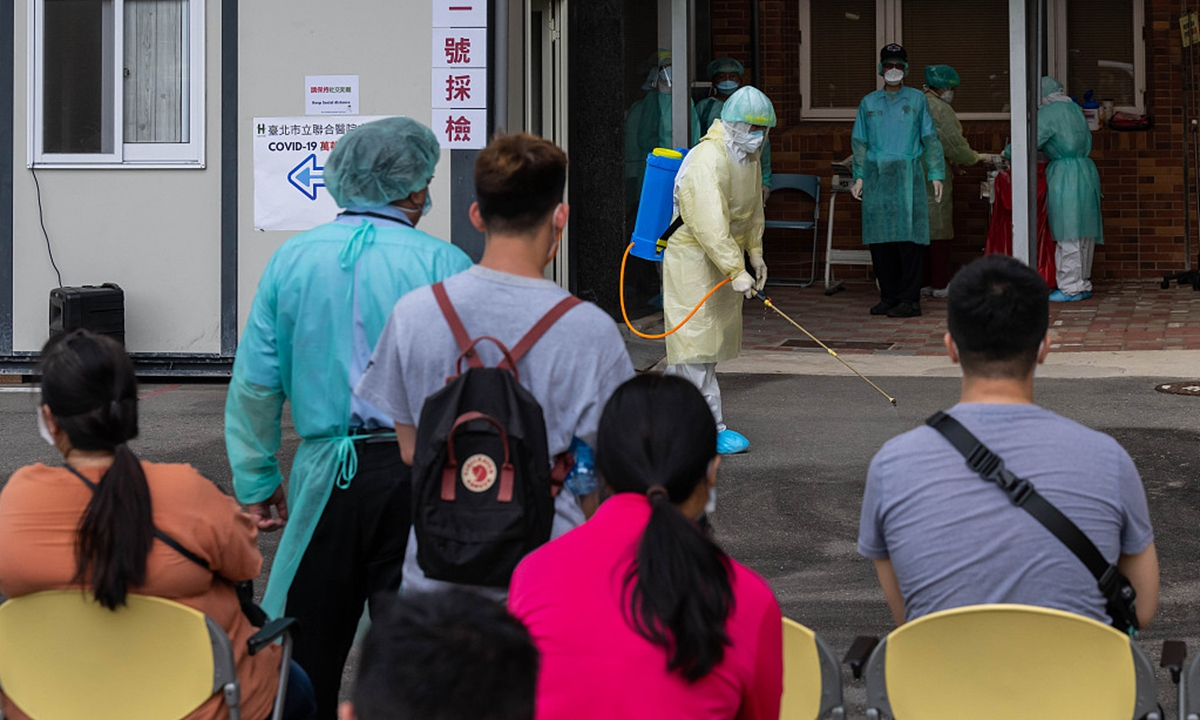 A healthcare worker sprays disinfectant on the floor at a hospital while people wait in line for nucleic acid tests in Taipei, island of Taiwan, on Monday. Photo: VCG