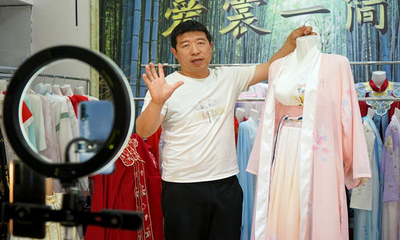 A merchant showcases Hanfu in Caoxian, East China's Shandong Province. Photo: Qi Xijia/GT