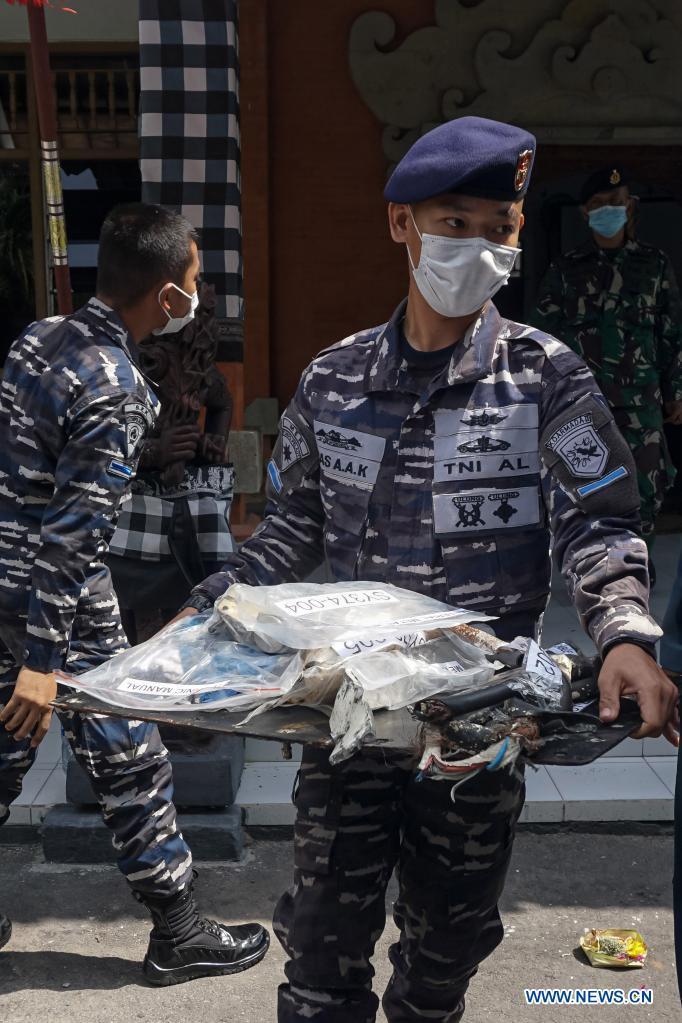 Seorang perwira TNI AL membawa bagian dari kapal selam Indonesia KRI Nanggala-402 usai jumpa pers di Denpasar, Bali, Indonesia, 18 Mei 2021 (Foto: Xinhua)