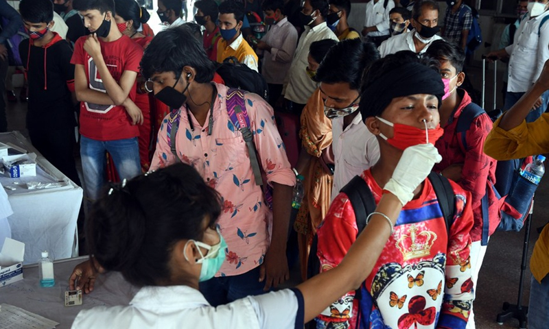 Health workers perform COVID-19 tests to passengers arriving at the Patna railway station in Patna, India, on May 22, 2021. Photo: Xinhua
