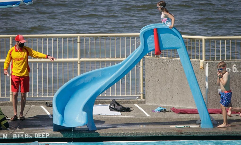 Children play a slide at the pool side during the first day of re-opening at the Kitsilano outdoor pool in Vancouver, British Columbia, Canada, May 22, 2021. Three of Vancouver's outdoor pools reopened Saturday. Due to the COVID-19 registration in place, anyone who wants to take a dip will have to register in advance due to pandemic-related restrictions on capacity.(Photo: Xinhua)