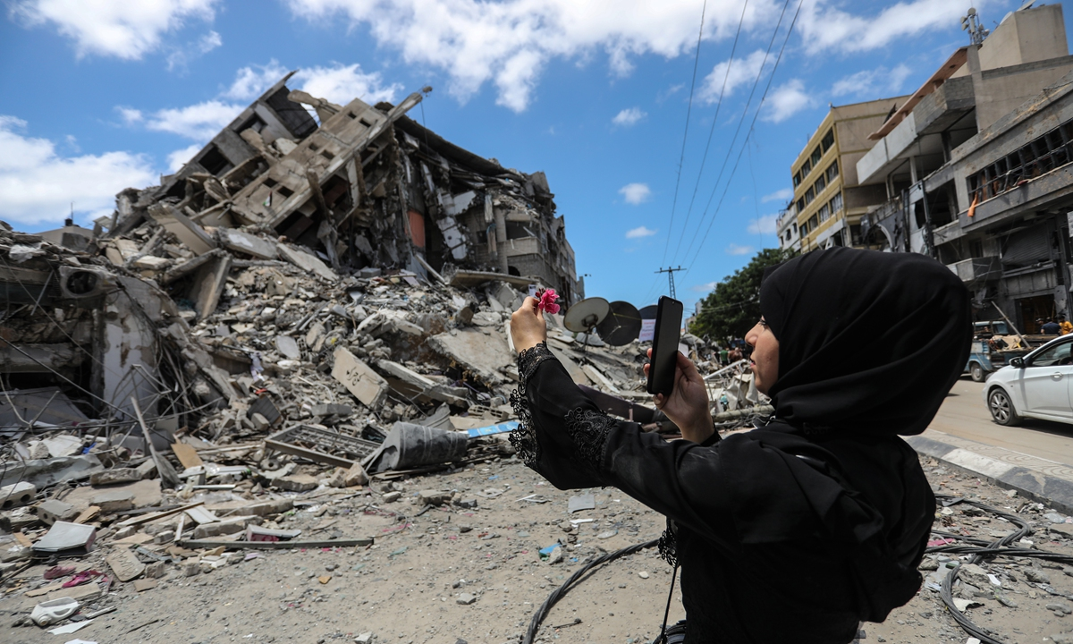 Palestinian woman takes a selfie near the rubble in Gaza city on Saturday, Gazans tried to piece back their lives after a devastating 11-day conflict with Israel that killed more than 200 people and made thousands homeless in the impoverished Palestinian enclave. Photo: VCG
