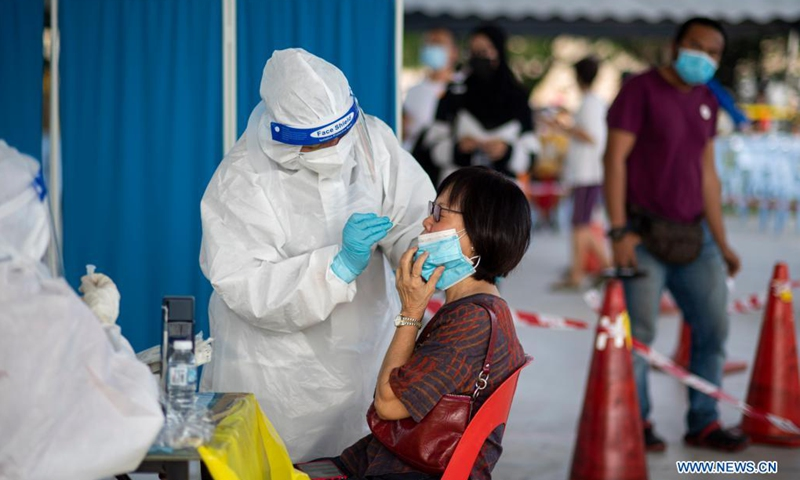 A medical worker takes a swab sample from a woman for COVID-19 test in Subang Jaya, Selangor, Malaysia, May 23, 2021. Malaysia on Sunday reported 6,976 new COVID-19 infections in the highest daily spike since the outbreak, bringing the national total to 512,091, the health ministry said.(Photo: Xinhua)
