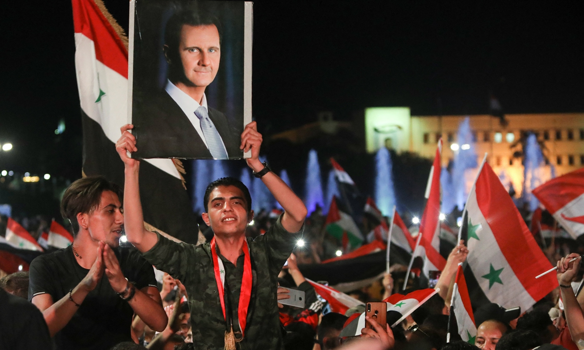 Syrians wave national flags and raise a portrait of their president as they celebrate in the streets of the capital Damascus, a day after an election set to give President Bashar al-Assad a fourth term, on Thursday. The election held in government-held areas was the second presidential vote in Syria since the start in 2011 of a war that has left over 388,000 dead. Photo: AFP