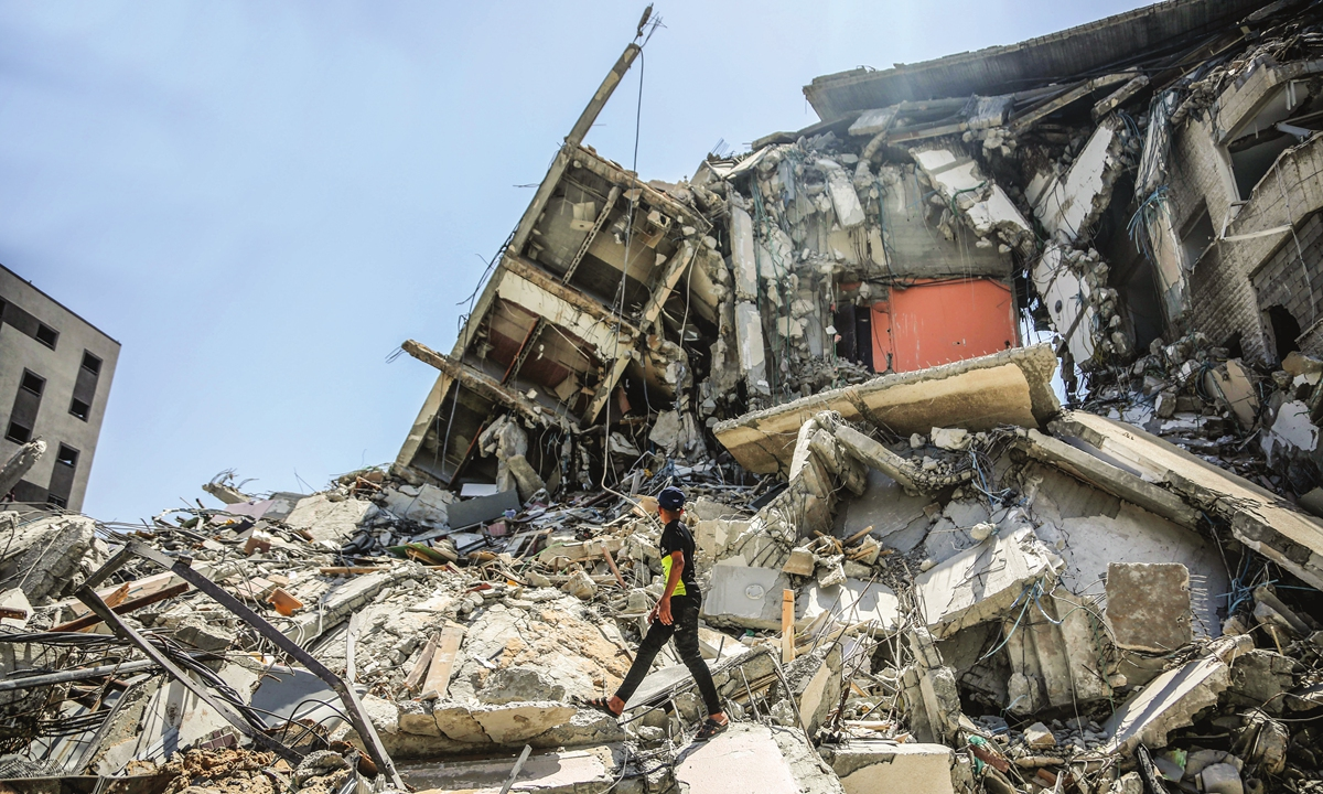 A Palestinian walks over the rubble accumulated in Gaza, following the cease-fire agreement between Gaza and Israel on Sunday. Photo: VCG