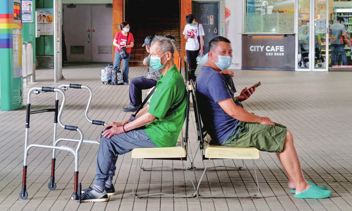 Local residents wearing masks wait for buses in New Taipei City on May 15. Photo: AFP