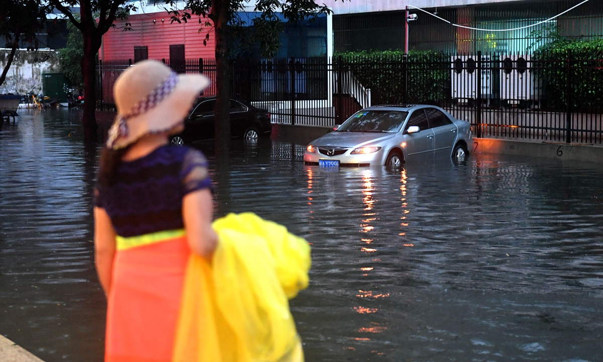 A resident looks at vehicles stuck in the water as a strong rainstorm struck Fuzhou, capital of East China's Fujian Province on Thursday, and caused severe flooding in the streets. Local weather authorities issued an orange alert, the second-highest in China's four-tier warning system, on Thursday evening and forecast precipitation to reach more than 50 millimeters in three hours in urban areas of Fuzhou. Photo: cnsphoto