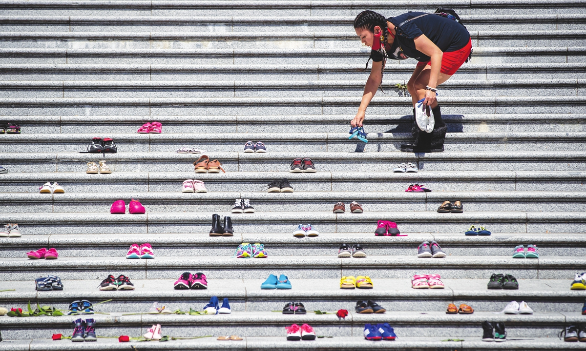 Lorelei Williams puts one of 215 pairs of children's shoes on the steps of the Vancouver Art Gallery. Photo: VCG
