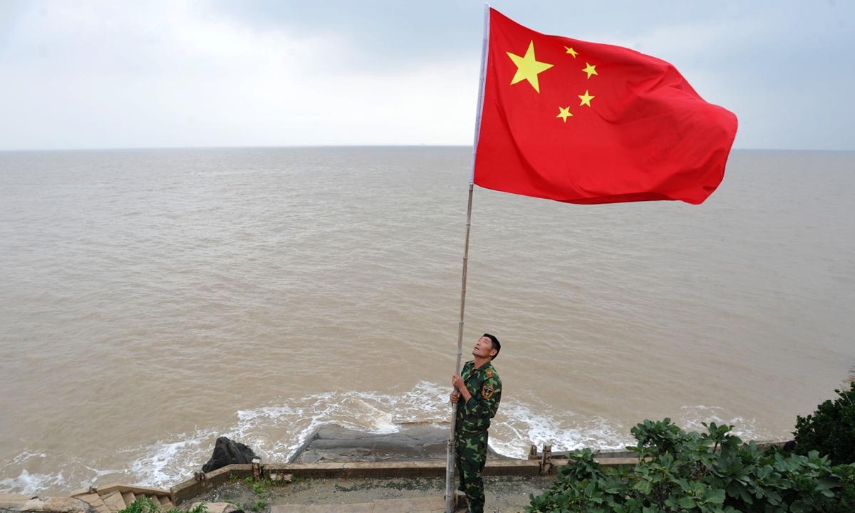Wang Jicai raises the national flag on the island. Photo: VCG