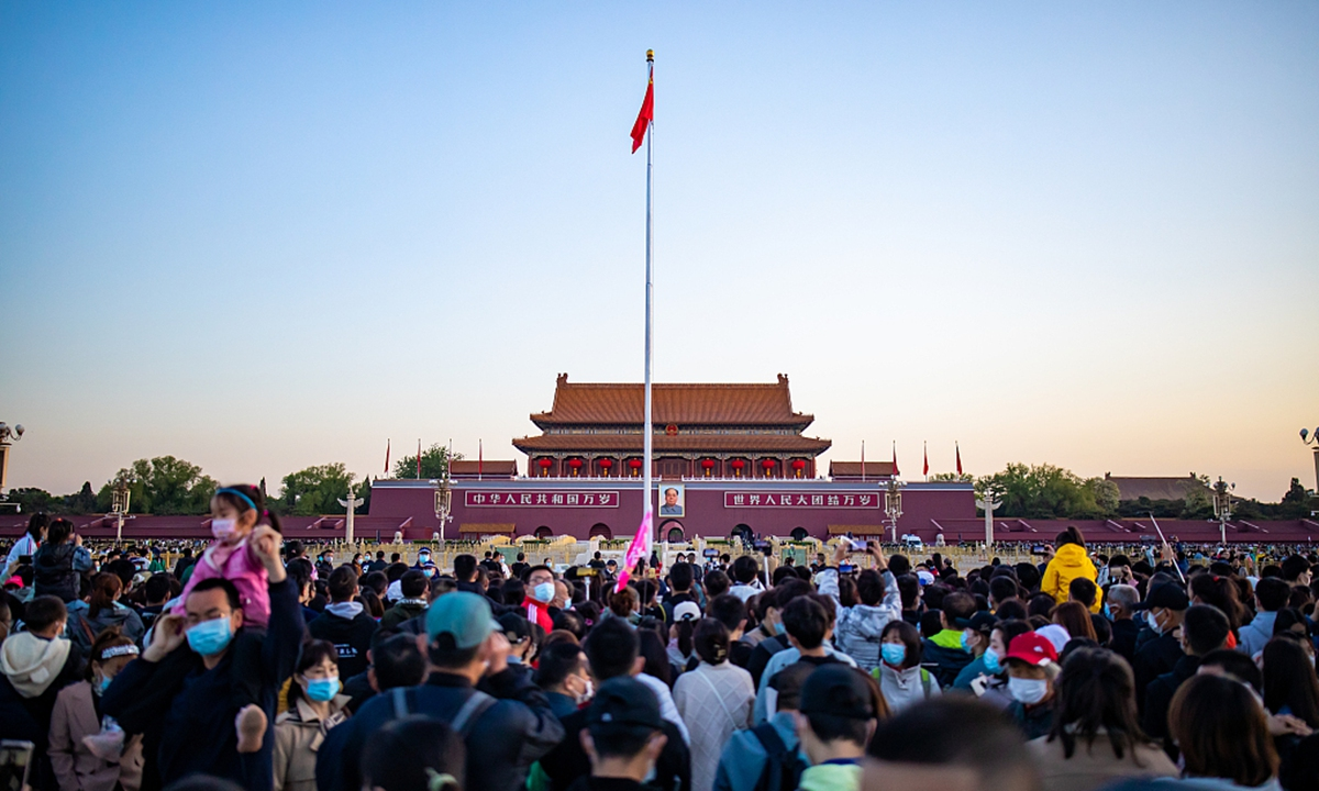 Tens of thousands of people witness a grand flag raising ceremony in Tiananmen Square in May. Photo: VCG