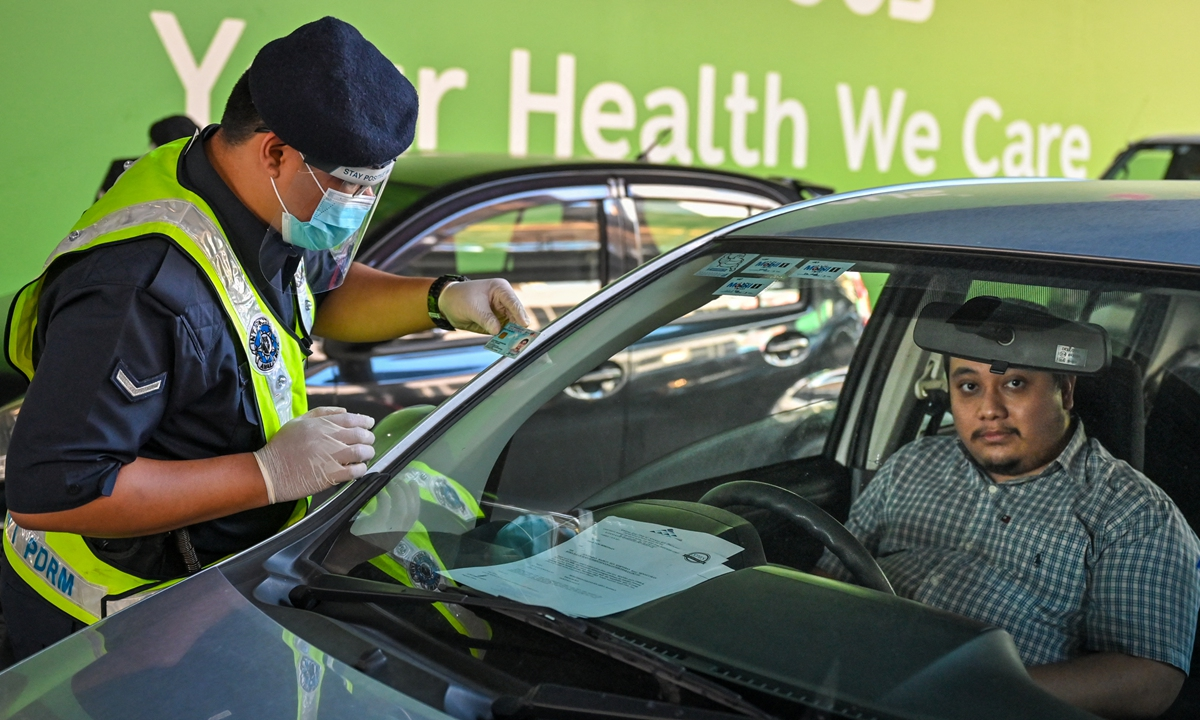 A policeman inspects the travel documents of a motorist at a roadblock during the nationwide lockdown amid fears over the spread of COVID-19 in Kuala Lumpur, Malaysia on Tuesday. Photo: AFP