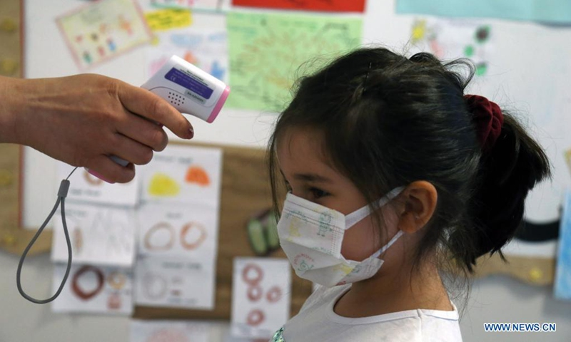 A child has her temperature checked at a kindergarten in Ankara, Turkey, on June 1, 2021. Turkey entered a new stage on Tuesday in the fight against COVID-19 after the government further eased the anti-coronavirus restrictions. The weekend lockdown was lifted on Saturdays, and weekday night curfews were postponed by an hour. Restaurants and cafes, and sports facilities also became operational with a limited number of guests.(Photo: Xinhua)