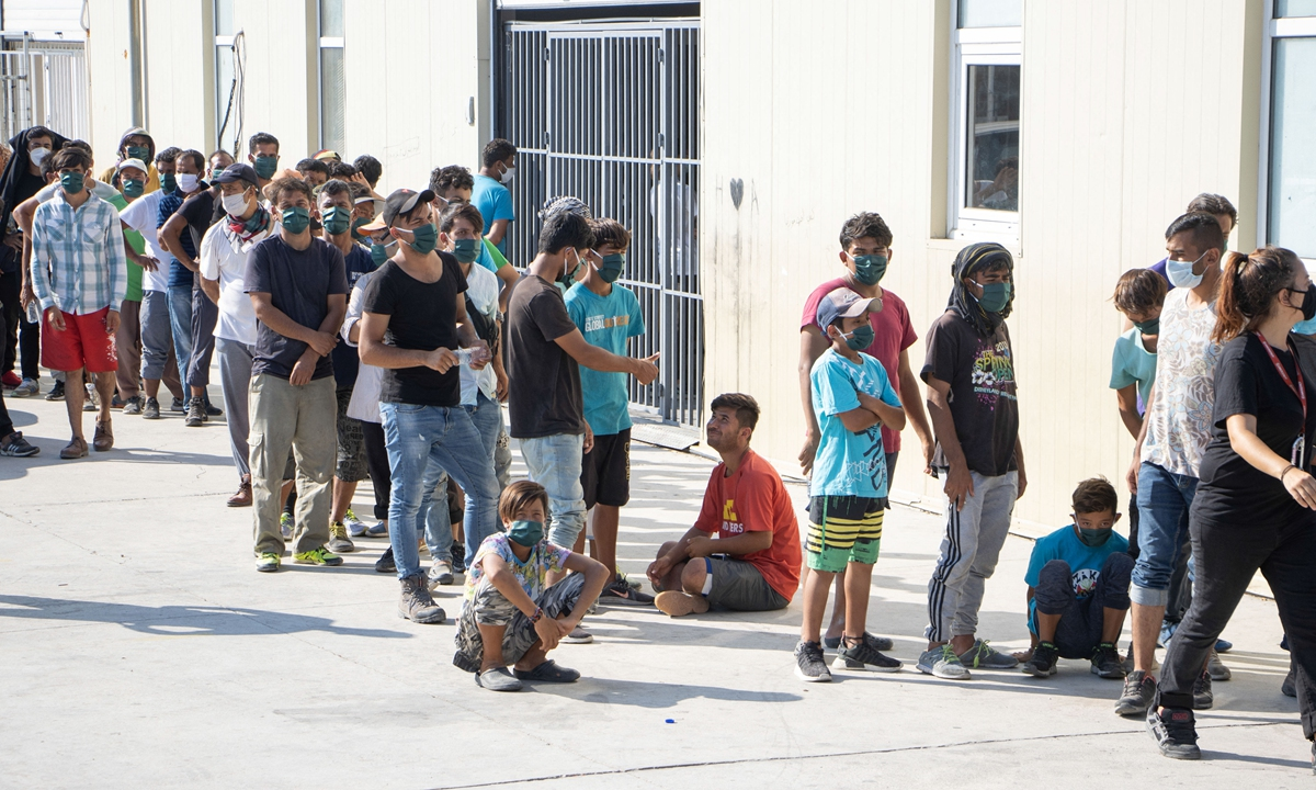 Asylum seekers wait in line to have their body temperature tested from Team Humanity Denmark NGO on Lesbos Island, Greece on September 20, 2020. Photo: AFP