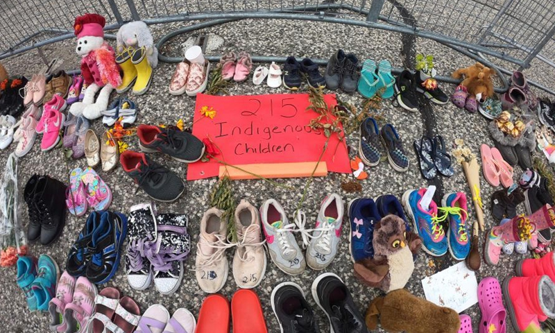 Children's shoes, dolls, flowers with notes at the front of Legislative Assembly of Ontario, Toronto, Ontario, Canada, June 2, 2021.Photo:China News Service