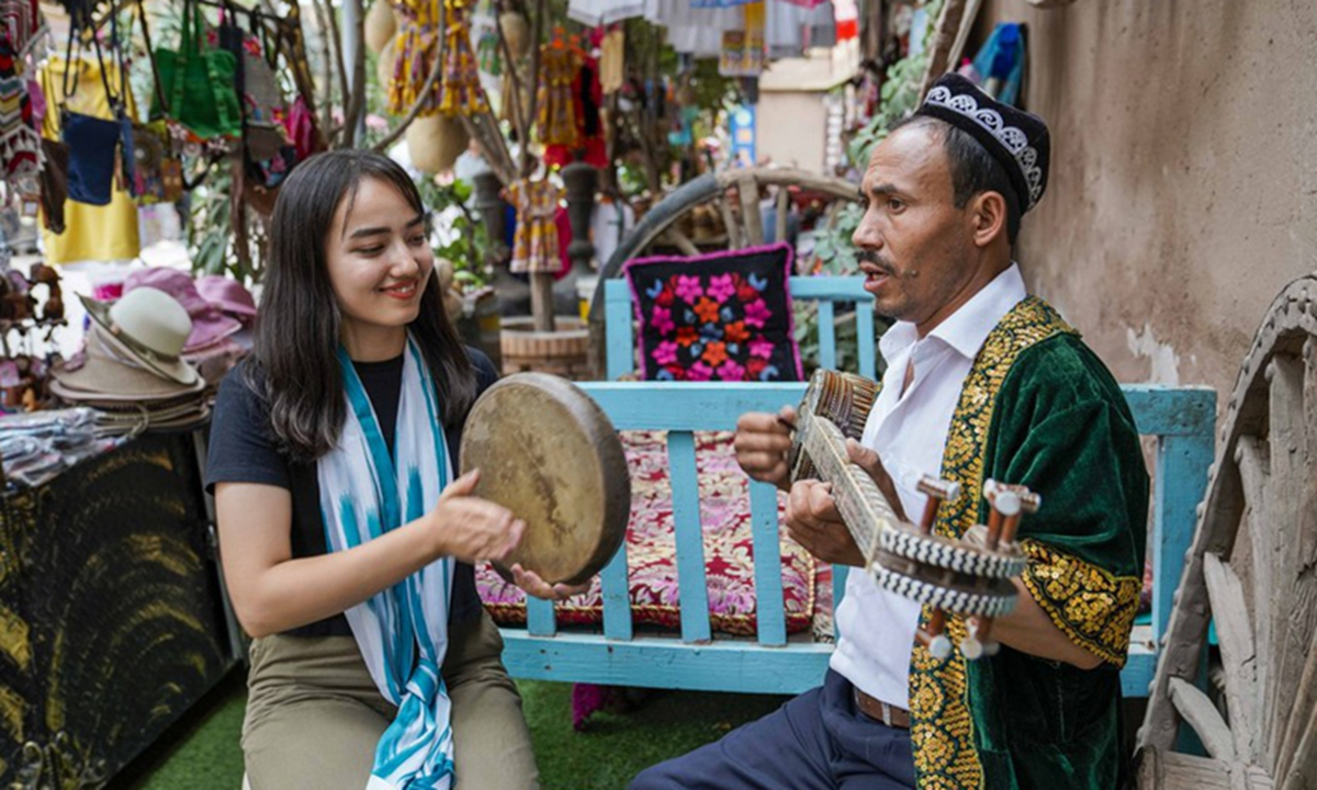 Local residents who are involved in the tourism business play music for tourists in the old town of Kashgar, northwest China's Xinjiang Uygur Autonomous Region, July 9, 2019. Photo:Xinhua