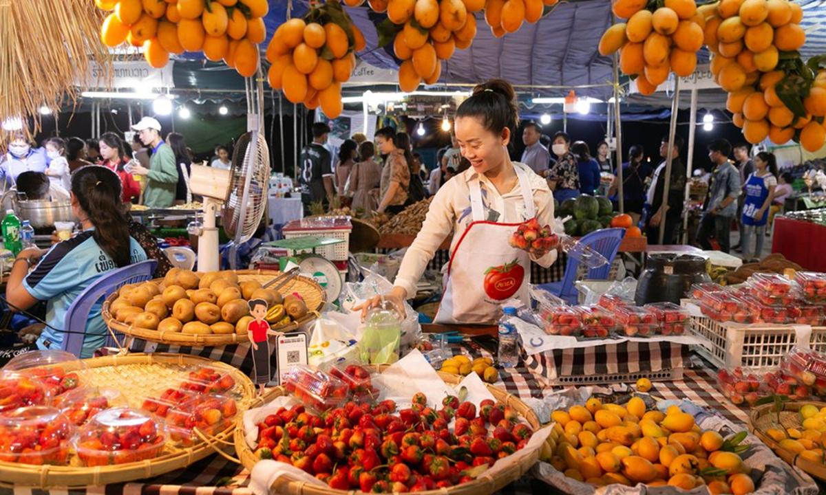 A vendor sells fruits at the Lao Food Festival in Vientiane, Laos, Feb. 26, 2021. (Photo by Kaikeo Saiyasane/Xinhua)