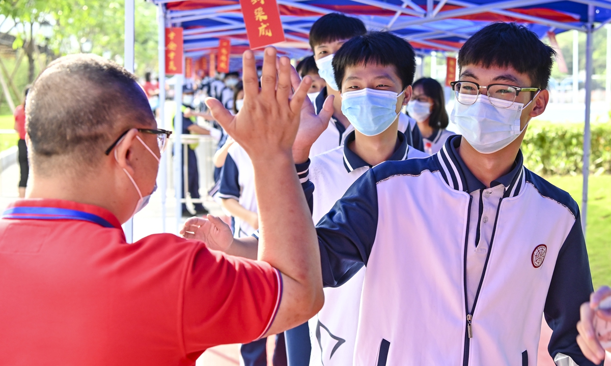 A teacher gives a high five to a student outside an examination point at a high school in Guangzhou, South China's Guangdong Province. A total of 10.78 million Chinese students across the country stepped into <em>Gaokao</em> examination rooms on Monday to take their final step toward college. Photo: VCG
