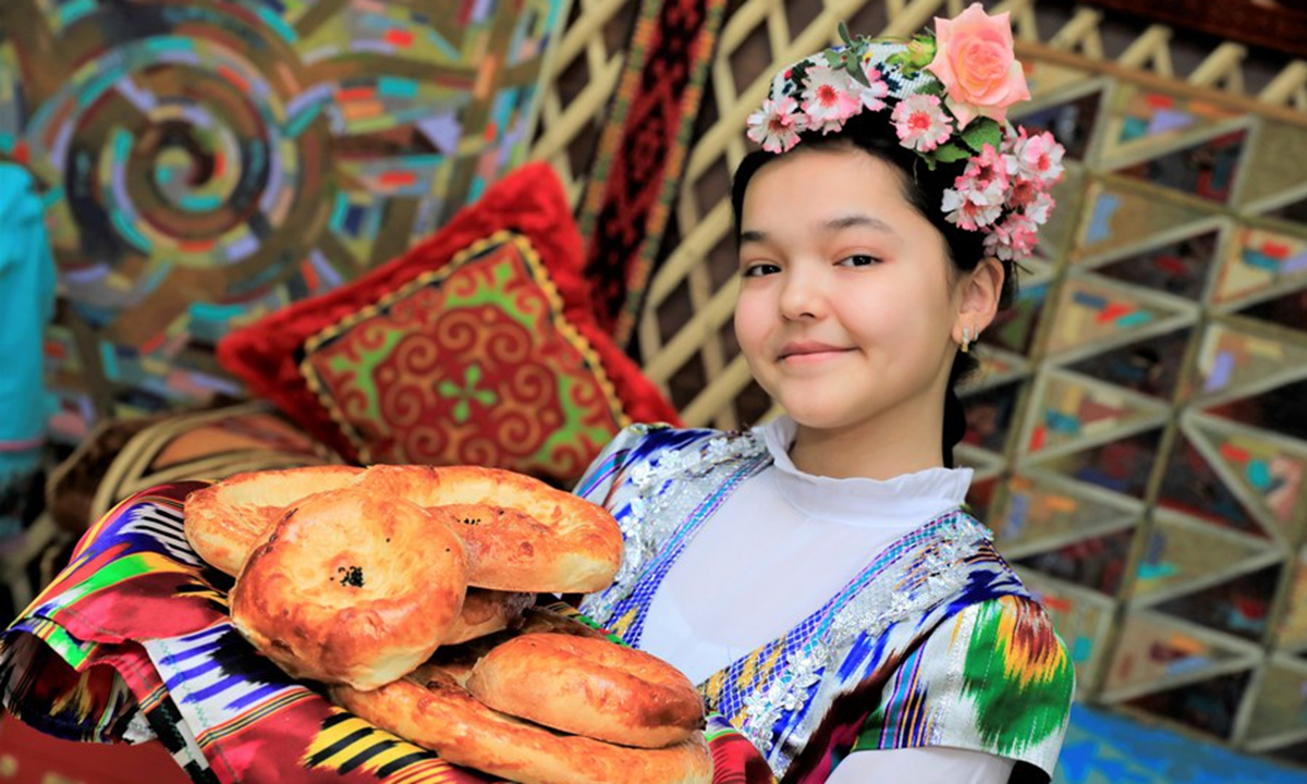 A girl shows traditional food during celebrations of Nauryz festival in Nur Sultan, Kazakhstan, March 19, 2021. (Photo by Kalizhan Ospanov/Xinhua)