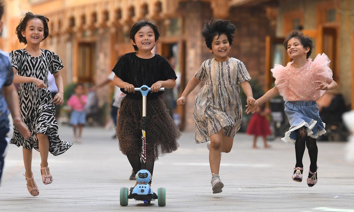 Local children play along Pigeon Lane in Tachengin Northwest China's Xinjiang Uygur Autonomous Regionin May 2020. Photo: Xinhua