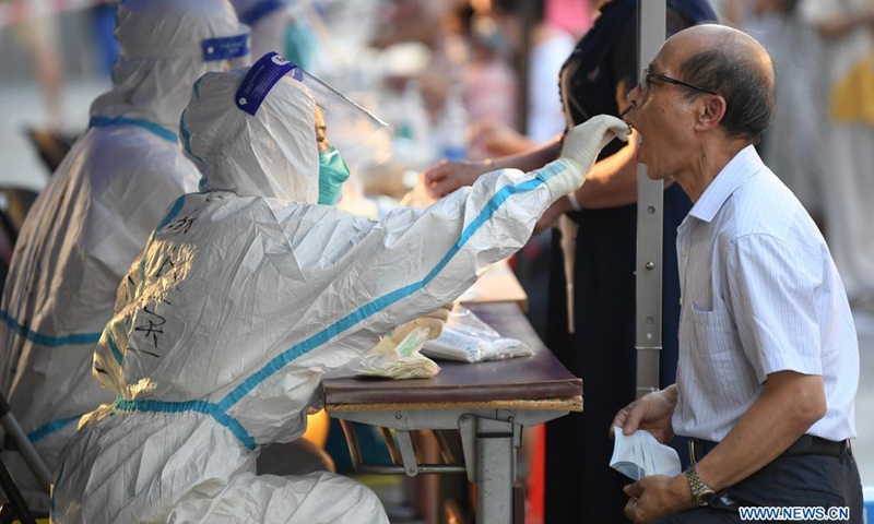 A medical worker collects a swab sample from a resident for COVID-19 nucleic acid testing in Liwan District of Guangzhou, south China's Guangdong Province, June 8, 2021. A new round of mass testing in high-risk areas of Baihedong Street and Zhongnan Street in Guangzhou started on Tuesday.(Photo: Xinhua)