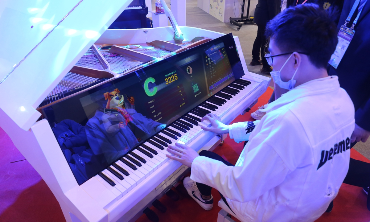 A visitor plays the piano with built-in artificial intelligence technology at the China (Shanghai) International Technology Fair on April 15. The piano is programmed to run intelligent error-correction and instruct the player. Photo: cnsphoto