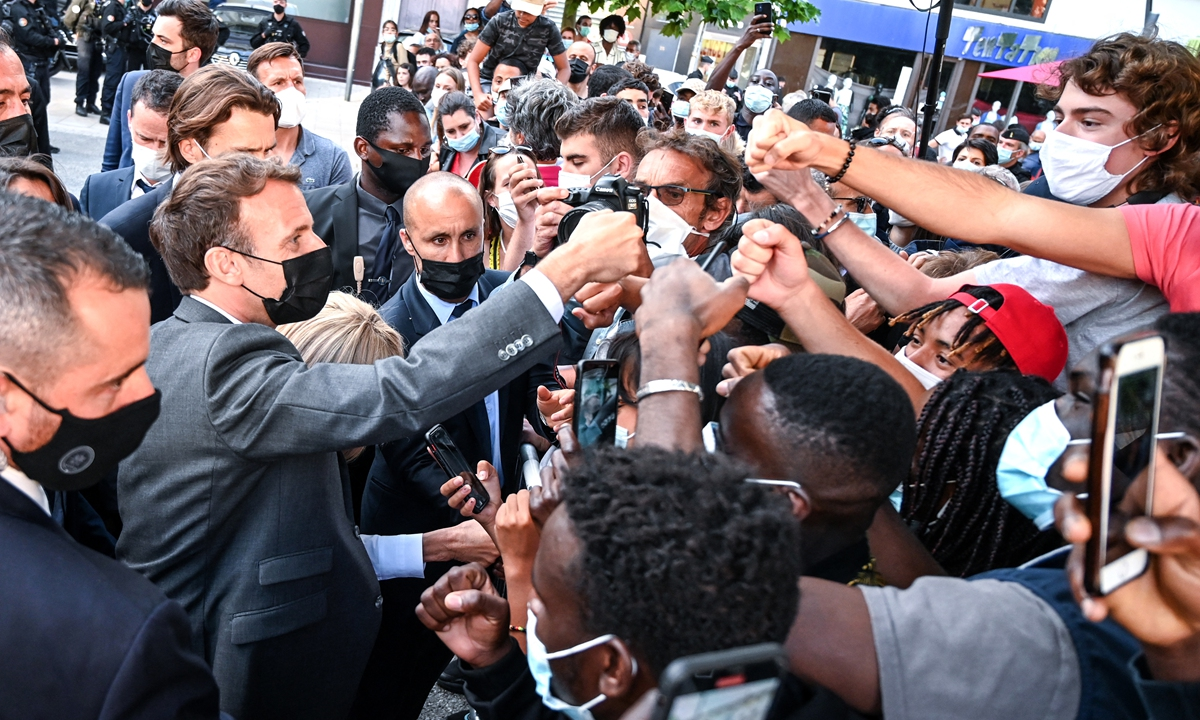 French President Emmanuel Macron (left) interacts with members of a crowd while visiting Valence on Tuesday during a visit in the French southeastern department of Drome, the second stage of a nationwide tour ahead of 2022's presidential election. Photo: AFP