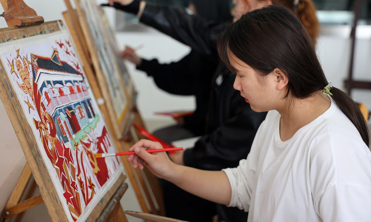 A student from a college in Nantong, East China's Jiangsu Province, paints a picture with a CPC revolutionary theme on April 28. Photo: VCG
