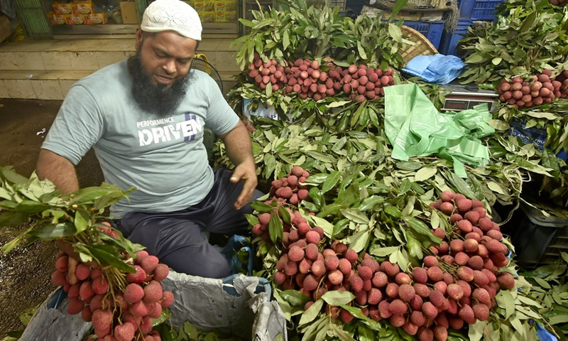 A vendor checks bundles of juicy and fleshy lychees for sale at a stall in Dhaka, Bangladesh on June 16, 2021.(Photo: Xinhua)