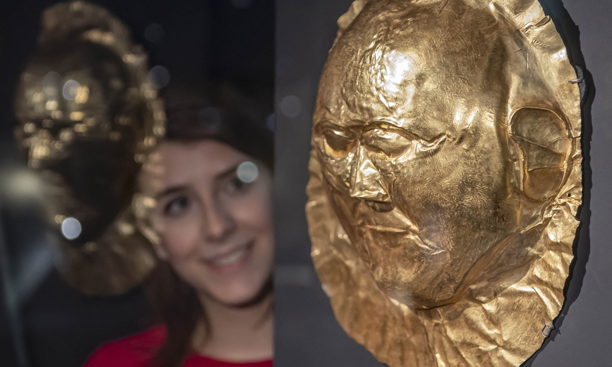 A woman at the Badisches Landes museum in Karlsruhe Castle looks at a golden tomb mask, part of the exhibition <em>Mycenae - The Legendary World of Agamemnon</em>, in Germany in 2018. Photo: AFP
